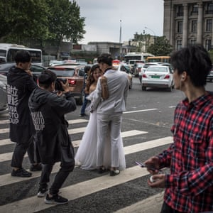 People pass a couple posing for their pre-wedding photos on a road in Wuhan