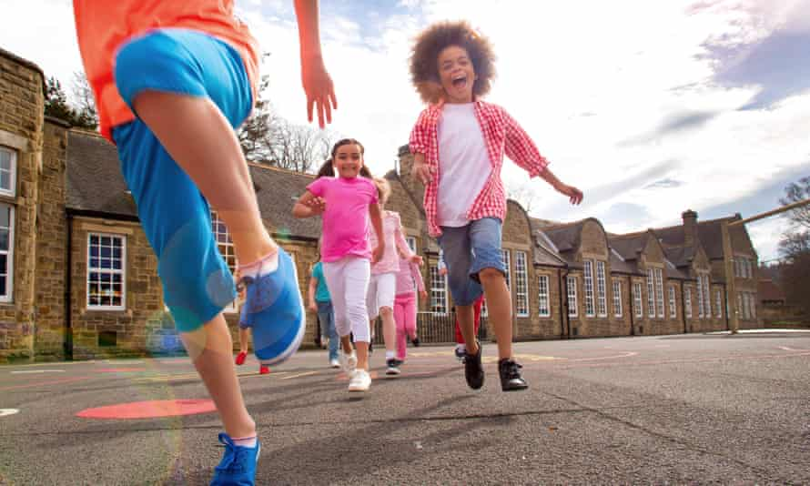 Children running across the school playground smiling. The children are running towards the camera. There are motion blurs and a sun flare. The children are casually dressed for summer. The school is visible in the background.