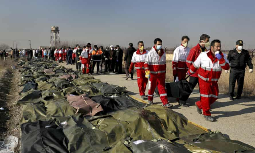 Rescue workers carry the body of a victim of a Ukrainian plane crash in Shahedshahr, near Tehran, Iran.
