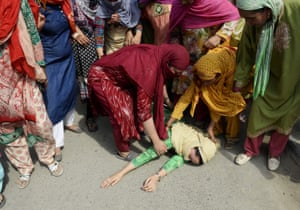 A woman in Anantnag, India, is helped by others after fainting during the funeral procession of slain militant Yawar Nissar