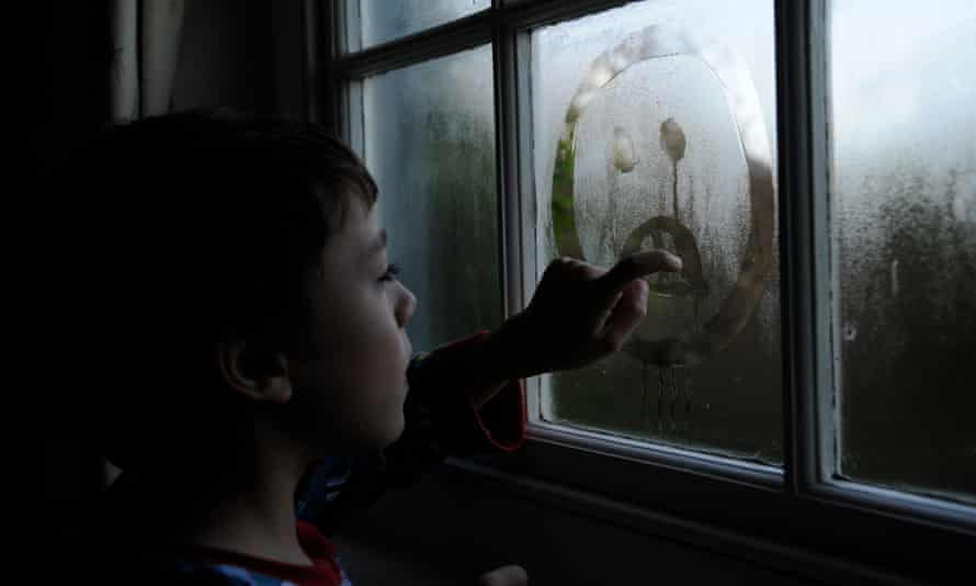 child drawing sad face in condensation on window