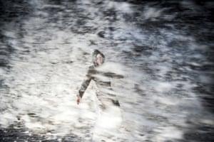 A woman enveloped in sea spray as she walks along the coast at Hirtshals