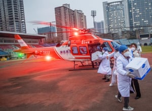 Concorde hospital staff carry medical materials from a helicopter