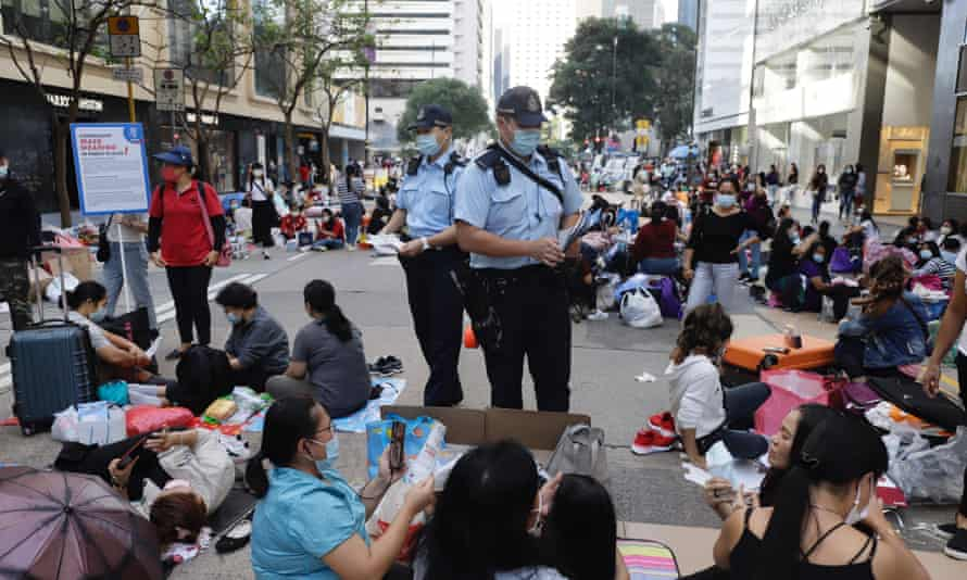 Police patrol central Hong Kong to tell women 'helpers' enjoying a day off to maintain social distancing.