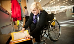 Young disabled woman in a wheelchair working filing documents.