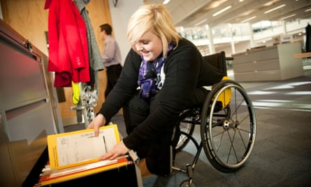 Young disabled woman in a wheelchair filing documents in a modern office