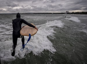 Timmendorfer Strand, Germany. A surfer jumps into the Baltic Sea as strong winds and unusually high waves attarct surfers to the normally quiet sea