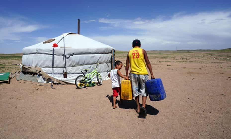 Orgilbayar and his little brother Munkhbat carry water to their father's ger in Khanbogd Sum, southern Gobi, Mongolia. The Oyu Tolgoi mine is visible in the background