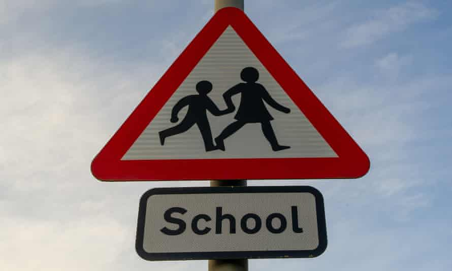 A school warning sign with two figures holding hands and walking