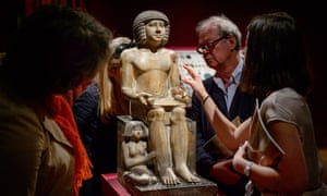 Members of the public and gallery staff examine the Northampton Sekhemka, an Egyptian painted limestone statue.