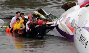Rescue personnel help passengers as they wait to be transported to land from the wreckage of a TransAsia ATR 72-600 turboprop plane that crash-landed into the Keelung river outside Taiwan's capital Taipei.