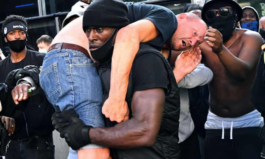 The story behind the photo … Patrick Hutchinson carries a white protestor to safety in London.