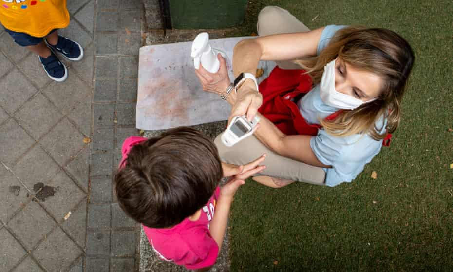 A child has her temperature checked before entering a preschool in Spain.