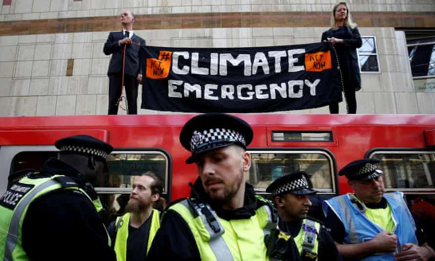 Police officers attend the scene of the Extinction Rebellion protest at Canary Wharf DLR station on 17 April