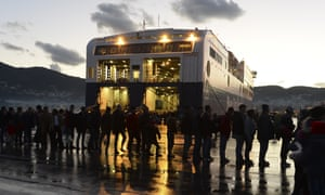 Refugees stand in a queue to board a ferry to Athens