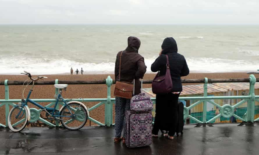 Tourists brave the weather in Brighton, Sussex, as rain and winds hit the south of the UK in late August.