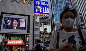 Japanese Prime Minister Shinzo Abe is seen on a large screen during a live press conference in Tokyo on 28 August 2020.