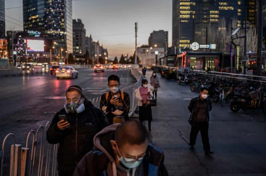 Chinese commuters wear protective masks as they line up in a staggered formation while waiting for a bus at the end of the work day on March 20, 2020 in Beijing, China.