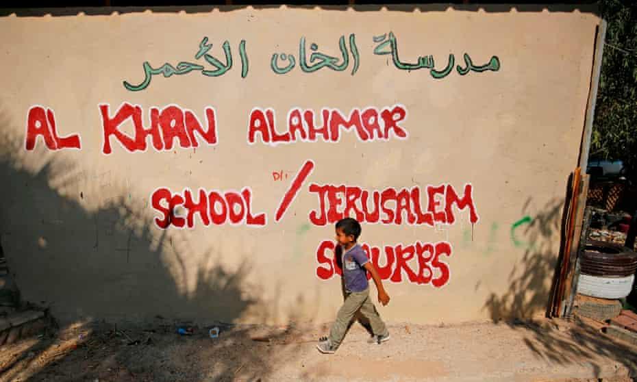 A Palestinian child walks past the wall of the school in Khan al-Ahmar