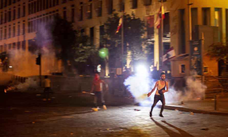 An anti-government protester throws back a tear gas canister in anti-government protests in Beirut on Thursday night.