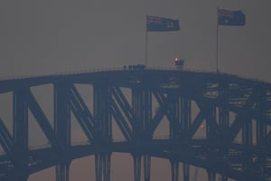 Climbers on the Sydney Harbour bridge as smoke haze from bushfires blankets the city.