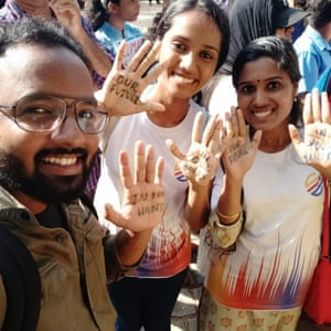 a man and two women in a selfie holding their hands up with handwritten notes on their palms saying our future in your hands