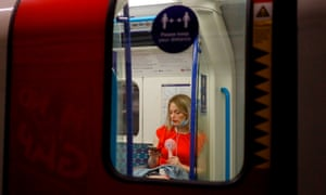 London: A woman fans herself as she looks at her smartphone on the tube