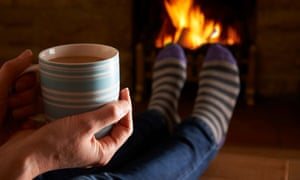 Person relaxing on a cold winter's night in front of the fire