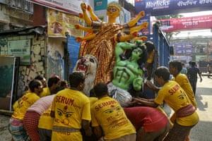 Kolkata, India: workers lift an idol of Hindu goddess Durga on to a truck before the Durga Puja festival
