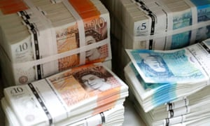 Wads of British Pound Sterling banknotes are stacked in piles.