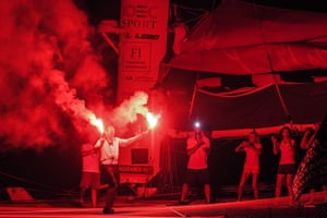 Francis Joyon celebrates winning a solo sailing race with flares onboard his yacht in Guadeloupe