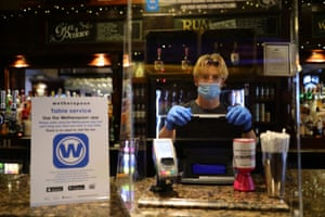 A member of staff in PPE waiting to serve drinkers at the reopening of Wetherspoons' Toll Gate pub, in Hornsey, north London.