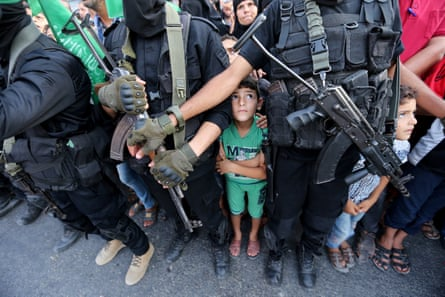 Palestinian boys stand next to Hamas militants as they take part in a military show