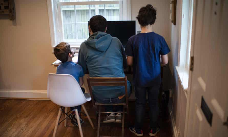 Two boys sitting with an adult in front of a computer at home