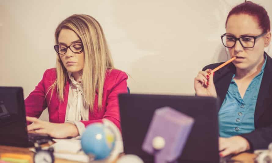 Two businesswomen working on laptops.