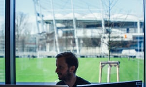 Andreas Schumacher at work in his office at Stuttgart's academy. In the background, sits the Mercedes-Benz Arena