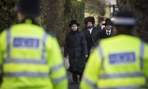Jewish men walk towards police officers in the Stamford Hill area in London