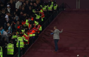 A Chelsea fan gets past the police line and walks over to goad the West Ham fans.