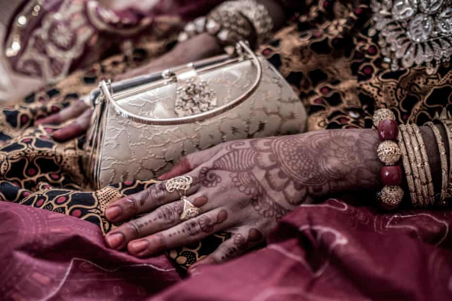 The decorated hands and full wedding attire of the bride on the wedding day