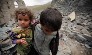A boy carries his sister, as he walks on rubble of a houseafter it was destroyed by a Saudi-led air strike in Yemen's capital Sana'a.