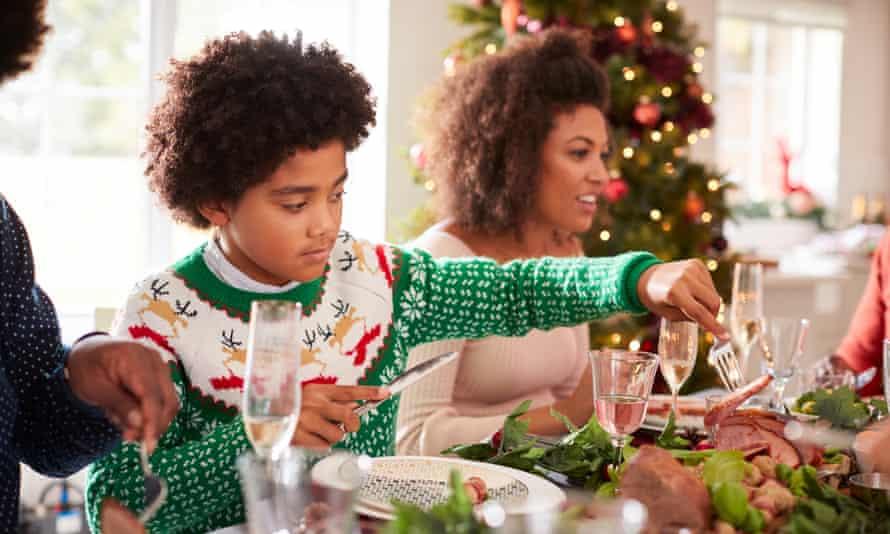 Boy serving himself roast turkey sitting at the Christmas dinner table