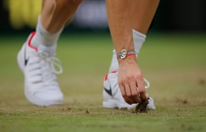 Adrian Mannarino puts back a divot of grass on Centre Court during his straight sets defeat to Novak Djokovic.