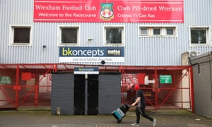 A man wearing a face mask of a character from the film Deadpool walks past the entrance to Wrexham's stadium on Thursday.