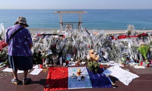 A woman stands by a makeshift shrine to victims of the Nice truck attack