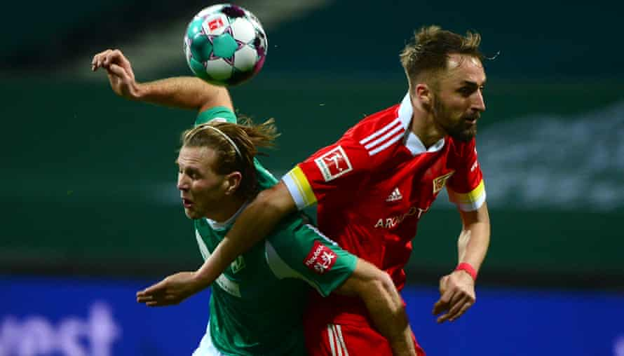 Werder's forward Niclas Fuellkrug, left, tangles with  and Union's Florian Huebner.