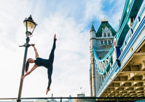 Pole fitness athlete Samantha Star holds a powerful pose by Tower Bridge