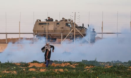 A Palestinian demonstrator and Israeli forces at the Gaza perimeter fence during protests in Khan Yunis, Gaza, on 18 January.