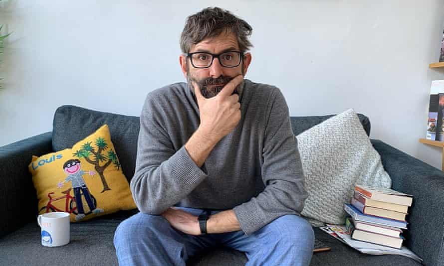Louis Theroux on sofa with mug and books.