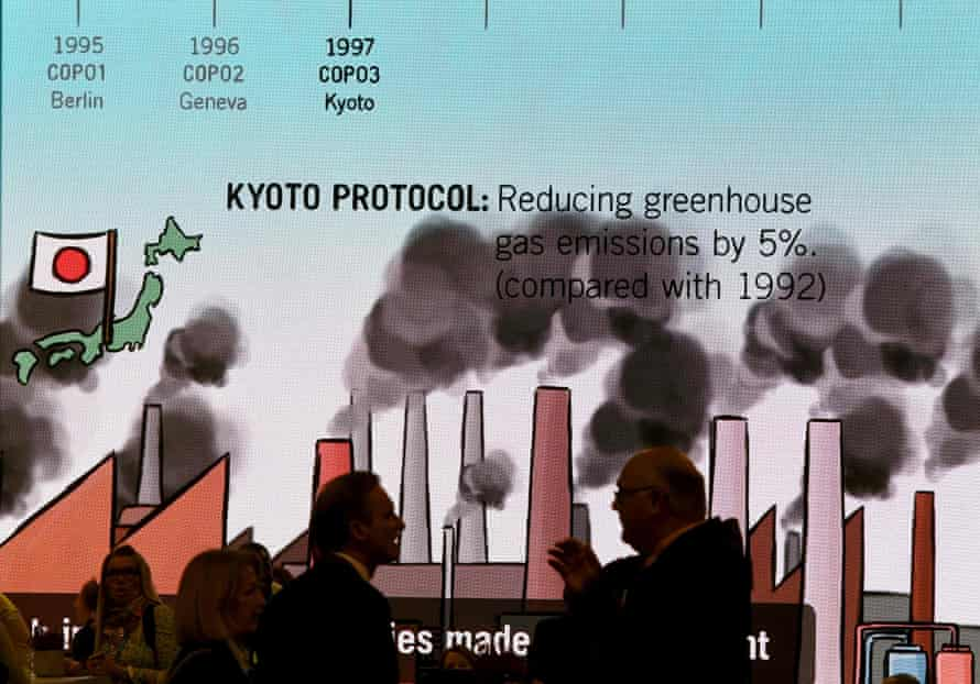 Visitors chat in front of a giant screen featuring information related to the Kyoto protocol at Cop23 in Bonn, Germany