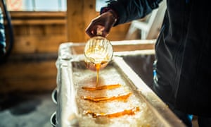 Pouring maple syrup onto snow at a sugar shack to make maple sugar taffy.